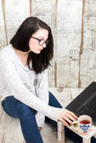 Student girl is wearing pair of glasses is studying on laptop wh Royalty Free Stock Images