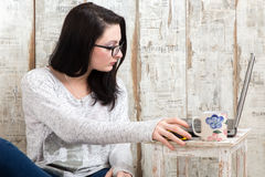 Student girl is wearing pair of glasses is studying on laptop wh. Ile drinking tea from her mug Stock Photo