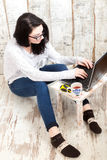 Student girl is wearing pair of glasses is studying on laptop wh. Ile drinking tea from her mug Royalty Free Stock Image