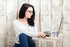 Student girl is wearing pair of glasses is studying on laptop wh. Ile drinking tea from her mug Royalty Free Stock Images