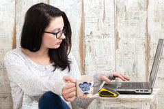Student girl is wearing pair of glasses is studying on laptop wh. Ile drinking tea from her mug Stock Photography