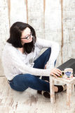 Student girl is wearing pair of glasses is studying on laptop wh. Ile drinking tea from her mug Stock Image