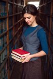 Student girl or woman with books in library. Stock Images