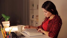 Student girl or woman reading book at night home stock video