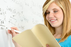 Student girl writing maths on white board Stock Photo