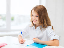 Student girl writing in notebook at school Stock Photography