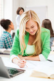 Student girl writing in notebook at school Royalty Free Stock Images