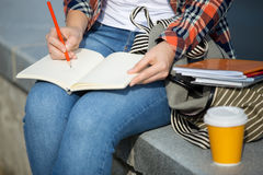 Student girl writing in an open notebook with a pencil Royalty Free Stock Photography