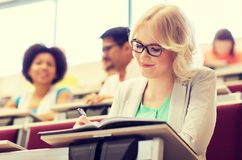 Student girl writing to notebook in lecture hall royalty free stock images