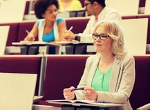 Student girl writing to notebook in lecture hall stock photo