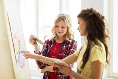 Student girls or artists painting at art school. Art school, creativity and people concept - happy student girls or artists with easel, palettes and paint brush Royalty Free Stock Photos