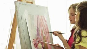Student girls with easel painting at art school stock video