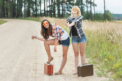 Student girls funny grimacing and hitchhiking Royalty Free Stock Photography