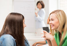 Student girls gossiping at school Royalty Free Stock Images