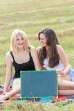 Student girls holding board for writing Royalty Free Stock Photos