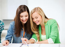 Student girls pointing at notebook at school Stock Photo