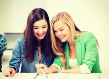 Student girls pointing at notebook at school Stock Photos