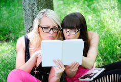 Student girls reading the book. Two pretty student girls reading book with no title Stock Photography