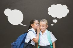 Student girls with speech bubbles whispering against grey background royalty free stock images