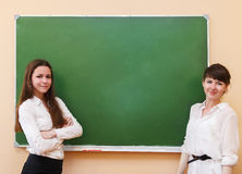 Student girls standing near blackboard Royalty Free Stock Photography
