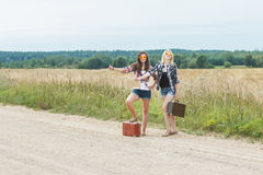 Student girls wearing sunglasses hitchhike on road Royalty Free Stock Photos