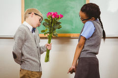 Student giving flowers to another student Royalty Free Stock Image