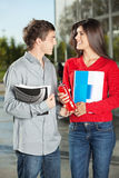 Student Giving Juice Bottle To Friend On Campus Royalty Free Stock Photo