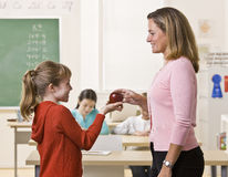 Student giving teacher apple Stock Photography