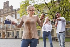 Student in glasses feeling awful after spilling her drink. Spilling drink. Blonde-haired student in glasses feeling awful after spilling her drink on her shirt Royalty Free Stock Photos
