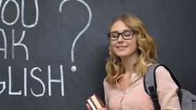 Student in glasses holding books, do you speak english on blackboard, education. Stock footage stock video