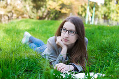 Student with glasses lying on grass Royalty Free Stock Image