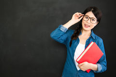 Student with glasses and textbook standing in front of blackboar Stock Image