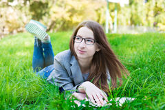 Student with glasses thinking on grass Stock Image