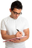 Student in glasses writes in book Royalty Free Stock Photos
