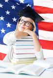 Student in graduation cap. Happy student in graduation cap with stack of books over american flag Stock Photography
