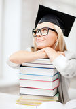 Student in graduation cap. Business and education concept - happy student in graduation cap with stack of books Royalty Free Stock Image