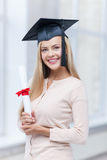 Student in graduation cap with certificate Stock Images