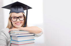Student in graduation cap. Education concept - picture of happy student in graduation cap with stack of books Stock Images