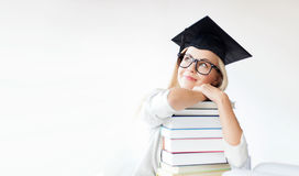 Student in graduation cap. Education concept - picture of happy student in graduation cap with stack of books royalty free stock photos
