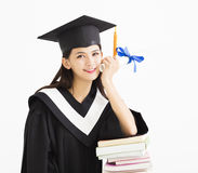 Student in graduation cap with stack of books. Happy student in graduation cap with stack of books Royalty Free Stock Photo