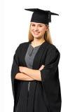 Student In Graduation Gown med korsade armar Arkivfoto