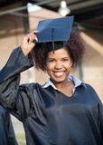 Student In Graduation Gown Wearing Mortar Board On Stock Image