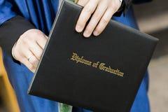 Student graduiert Stellung in Folge und Holding seine Diplome Stockfotografie