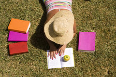 Student at the grass. A student relaxing at the grass of the school park (the pages in the book are my self printed Stock Photography