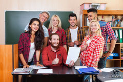 Student Group Looking At Paper Document With Professor Sitting Desk, Young People Teacher Discuss Royalty Free Stock Image