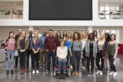 Student group standing in atrium under a big AV screen royalty free stock photo