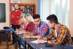 Student Group Write Test, Professor Observing, Jonge Diverse Mensen Sit Desk University Classroom Examination royalty-vrije stock afbeelding