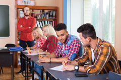 Student Group Write Test, Professor Observing, Young Diverse People Sit Desk University Classroom Examination Royalty Free Stock Image