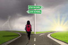 Student with guide to stay or leave school. Image of a female college student walking on the road with direction to stay or leave school stock photos