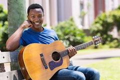 Student with guitar outdoors Royalty Free Stock Photo